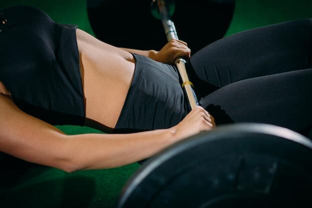 Het spier jonge meisje die van het geschiktheids mooie blonde een gewichtskruis opheffen past in de gymnastiek.