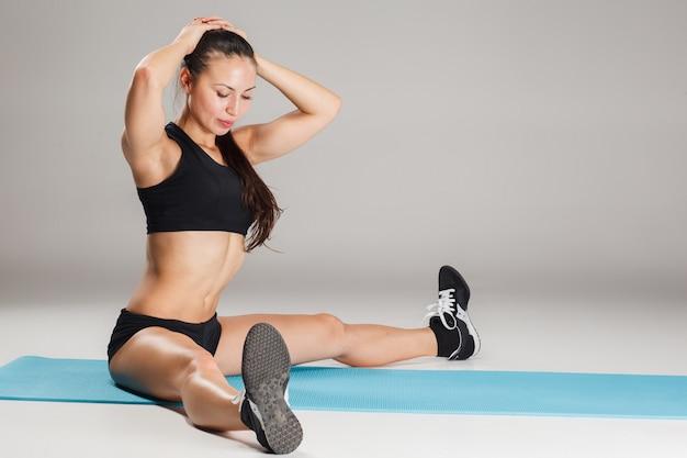 Het spier jonge vrouwenatleet uitrekken zich op grijs