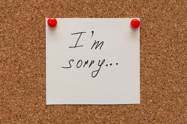 Het spijt me inscriptie tekst geschreven op wit papier vastgemaakt op cork board