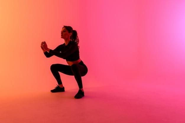 Het sportenmeisje op een heldere kleurenachtergrond doet oefeningen.