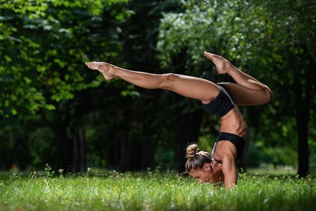 Het sportieve acrobaatmeisje bevindt zich op haar handen en maakt een acrobatisch element