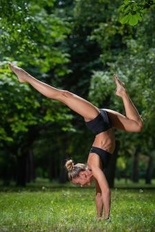 Het sportieve acrobaatmeisje die zich op haar handen bevinden, voert een acrobatisch element uit