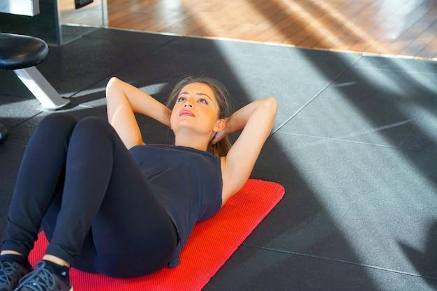 Het sportieve jonge vrouw doen zit-omhoog bij gymnastiek