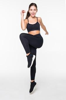 Het sportieve jonge vrouw springen geïsoleerd op witte muur