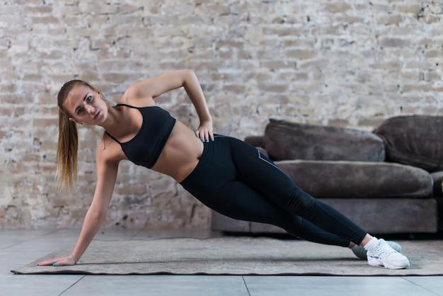 Het sportieve kaukasische meisje die zijplankster doen oefent werkende abs en schuine spieren binnen uit tegen bakstenen muur