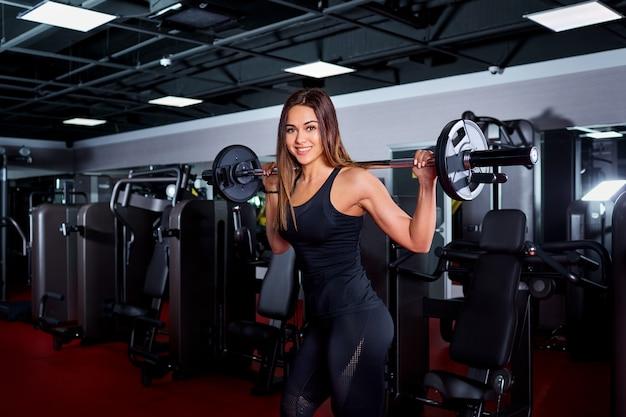 Het sportieve meisje heft de bar op. geschiktheids donkerbruine geschikte vrouw in gymnastiekverstand