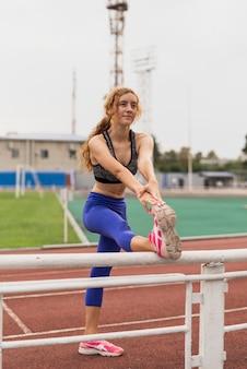 Het sportieve vrouw uitrekken zich bij stadion