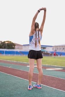 Het sportieve vrouw uitrekken zich vóór oefening