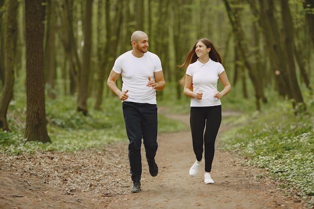 Het sportpaar brengt tijd in een de zomerbos door