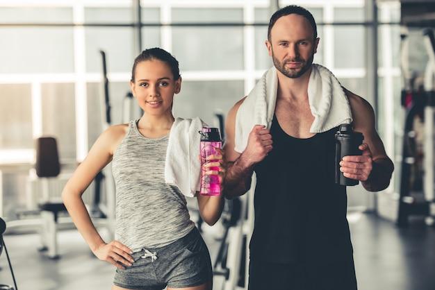Het sportpaar houdt fles water en schudbeker.