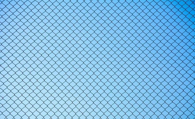 Het staal van het draadnetwerk op blauwe hemelachtergrond