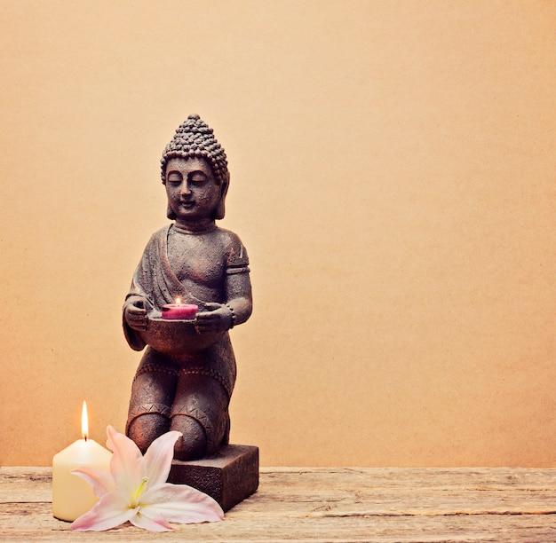 Het standbeeld van boedha met een kaars in handen op een houten achtergrond