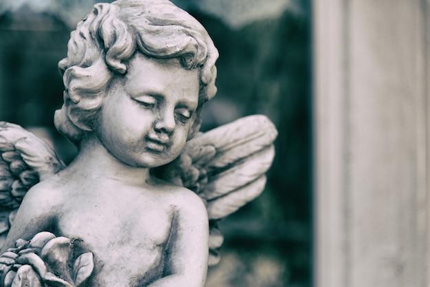 Het standbeeld van de schoonheidscupido van engel in uitstekende tuin op de zomer