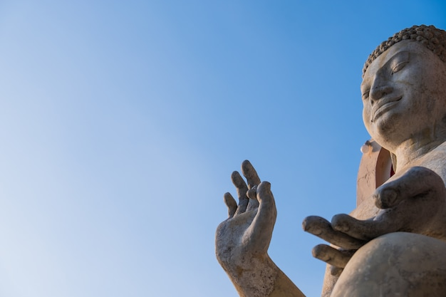 Het standbeeld van rotsboedha met blauwe die hemel voor amuletten van boeddhismegodsdienst wordt gebruikt.