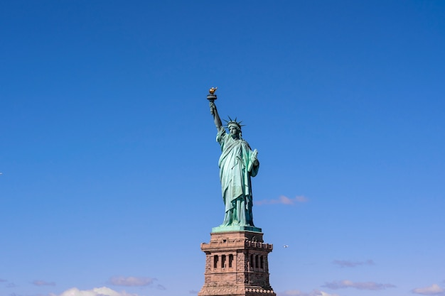 Het standbeeld van vrijheid onder de blauwe hemelachtergrond, lower manhattan, de stad van new york