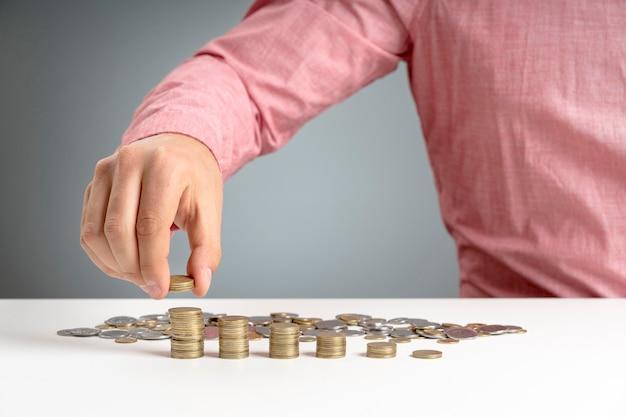 Het stapelen van de mens van muntstukken op bureau