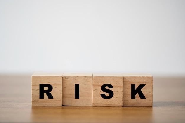 Het stapelen van houten die het scherm riskeren te formuleren op de tafel met kopie ruimte. risicobeheer concept.