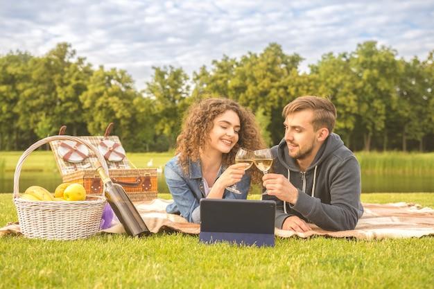 Het stel drinkt een wijntje tijdens een picknick in het park