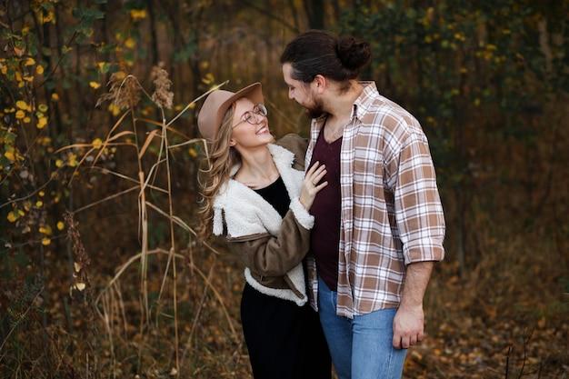 Het stel kijkt elkaar gelukkig aan tijdens een wandeling in de herfst