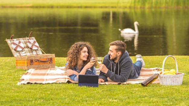 Het stel rust uit tijdens een picknick en drinkt een wijntje op de achtergrond van de rivier