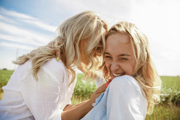 Het stel van de jonge lesbienne heeft de auto kapotgemaakt terwijl ze onderweg waren om uit te rusten. kussen en knuffelen op de kofferbak van de auto. relatie, problemen onderweg, vakantie, vakantie, huwelijksreisconcept.