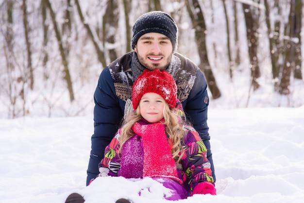 Het stellen van het meisje en van de vader tijdens spel met sneeuw