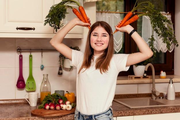 Het stellen van het meisje met wortelen in de keuken