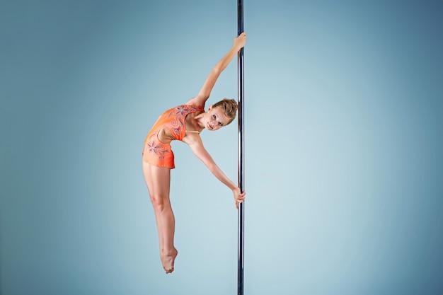 Het sterke en sierlijke jonge meisje dat acrobatische oefeningen op een pyloon uitvoert