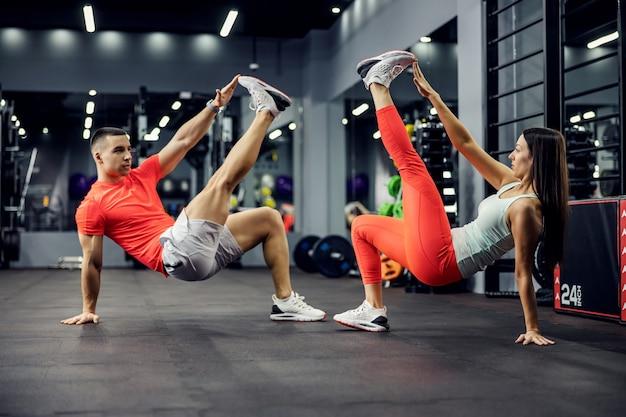 Het sterke fitnesskoppel doet veeleisende oefeningen voor de kern en het hele lichaam in de sportschool met apparatuur