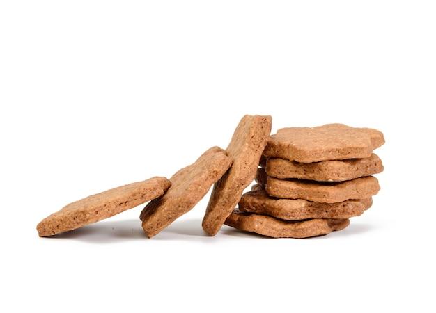 Het stervormige gebakken koekje van de chocoladepeperkoek dat op witte achtergrond, stapel wordt geïsoleerd