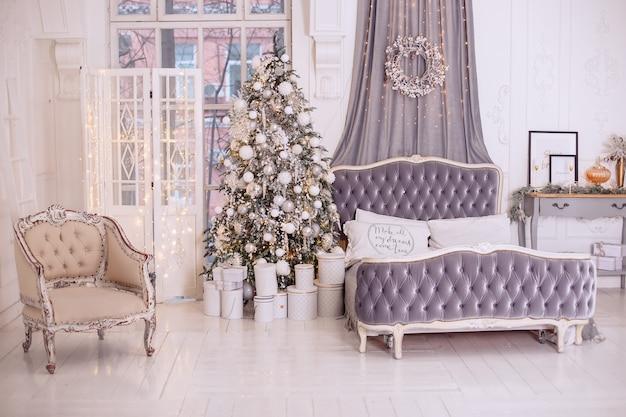 Het stijlvolle interieur van de nieuwjaarsslaapkamer is gedecoreerd in witte en grijze kleuren. groot zacht bed.