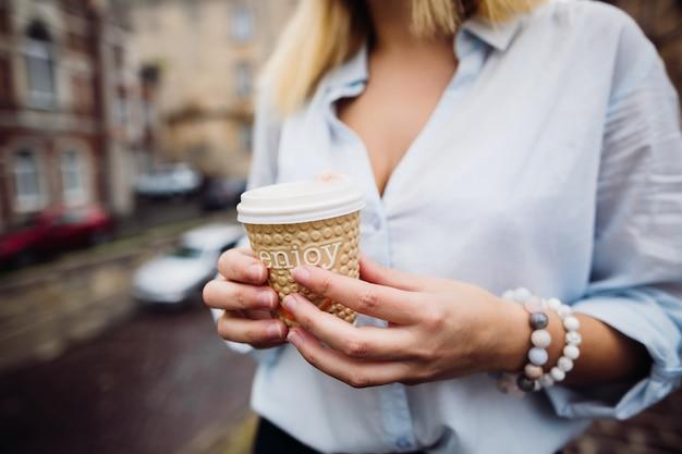 Het stijlvolle meisje houdt een kopje koffie