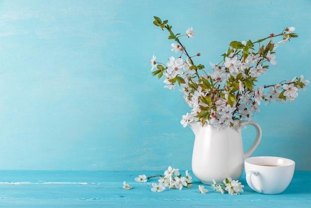 Het stilleven met een mooie bloesem van de de lentekers bloeit, koffiekop op blauwe houten lijst met exemplaarruimte