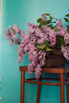 Het stilleven met lilac bloemen bundelt in een uitstekende bruine mand op een stoel, blauwe sjofele muurachtergrond