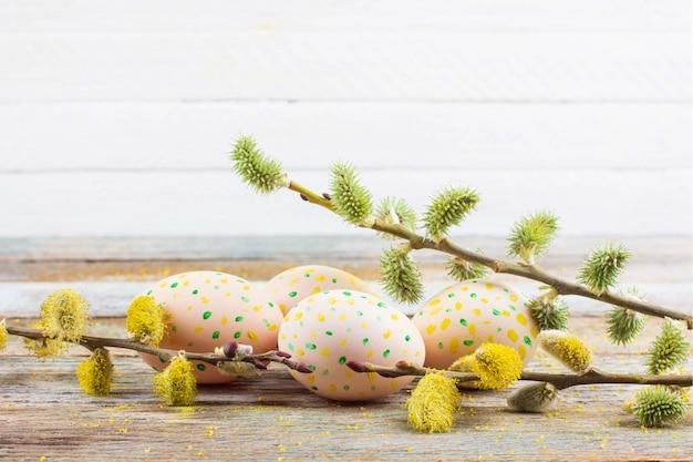 Het stilleven van de lentepasen van bloeiende wilgentakken en eieren op een houten retro lijst