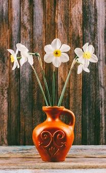 Het stilleven van een boeket van gele narcissen bloeit in een oude ceramische kruik op een houten uitstekende grungeclose-up