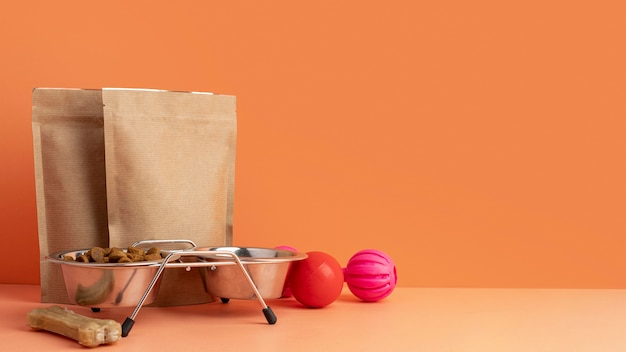 Het stillevenconcept van huisdieraccessoires naast papieren zakken voor voedsel voor huisdieren