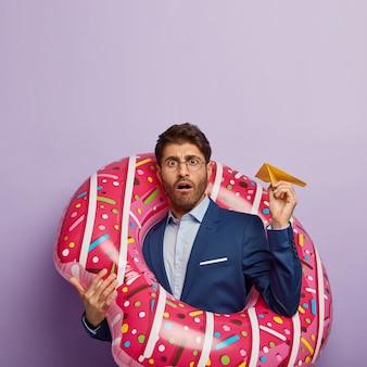 Het stomverbaasde zakenman poseren in stijlvol pak op kantoor