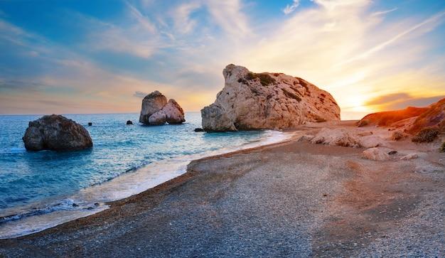 Het strand en de steen van aphrodite bij zonsondergang