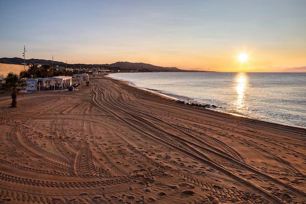 Het strand van badalona bij zonsopgang met voetafdrukken en autosporen op het zand