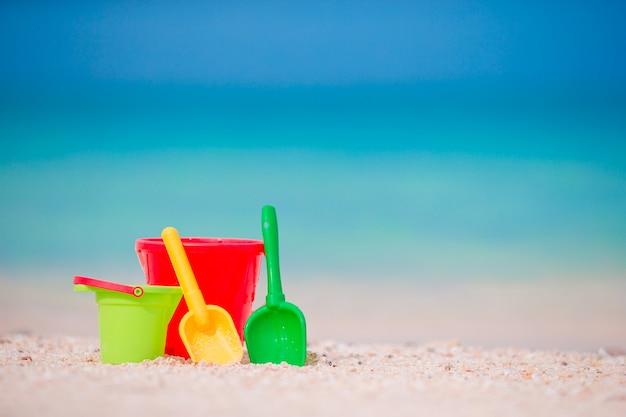 Het strandspeelgoed van het jonge geitje op wit zand. emmers en messen voor kinderen op het witte zandstrand na spelletjes voor kinderen
