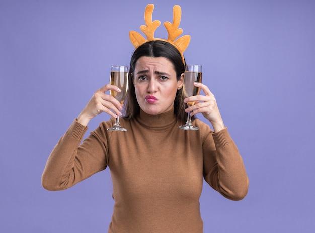 Het strelen van lippen jong mooi meisje die bruine sweater met de hoepel van het kerstmishaar dragen die twee glas champagne rond oren houdt die op blauwe achtergrond worden geïsoleerd