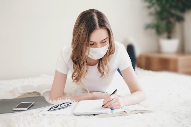 Het studentenmeisje die een medisch beschermend masker dragen ligt op het bed met boeken, notitieboekjes. jonge vrouw schrijft in een notitieblok thuis, afstandsonderwijs, thuisonderwijs, coronovirus, quarantaine