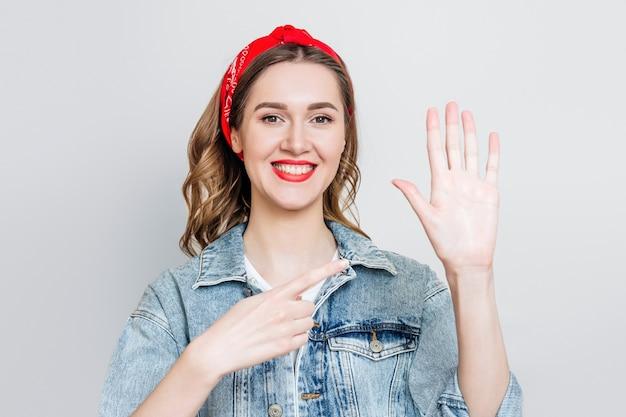 Het studentenmeisje glimlacht en richt op haar linkerhand die over grijze achtergrond wordt geïsoleerd