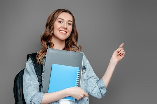 Het studentenmeisje houdt omslagen, notitieboekjes en richt een vinger op exemplaarruimte die op grijze muurachtergrond wordt geïsoleerd