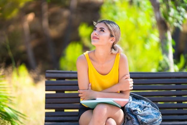 Het studentenmeisje van de tiener bij in openlucht omhoog het kijken terwijl het glimlachen