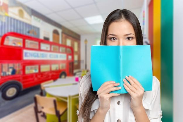 Het studentenmeisje verbergt zich achter het boek