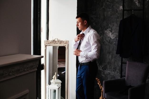 Het studioportret van bruidegom in wit overhemd past een rode band aan. bruidegoms ochtend. jonge lachende man in wit overhemd en zwarte broek past de stropdas. stijlvolle man trekt een pak aan in een stijlvol interieur.