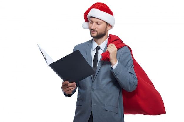 Het studioportret van de mens als de kerstman met volledige zak met stelt voor