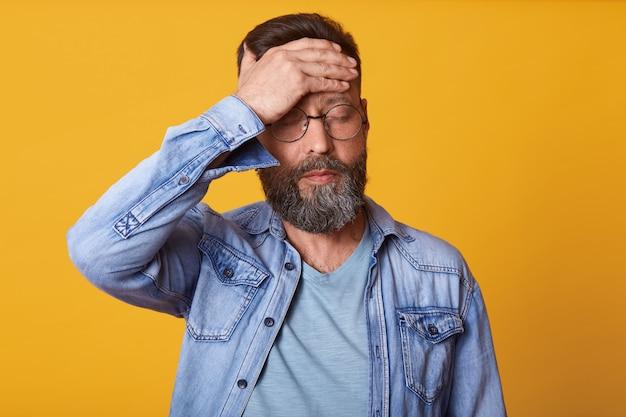Het studioschot van gespannen gebaarde jonge mens raakt zijn voorhoofd en hebbend hoofdpijn, gekleed denim, grijs t-shirt en glazen